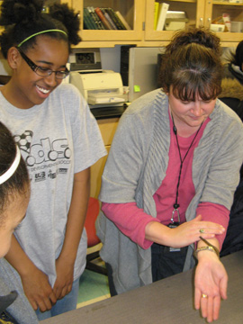 Angie, a teacher, showing students a millipede.